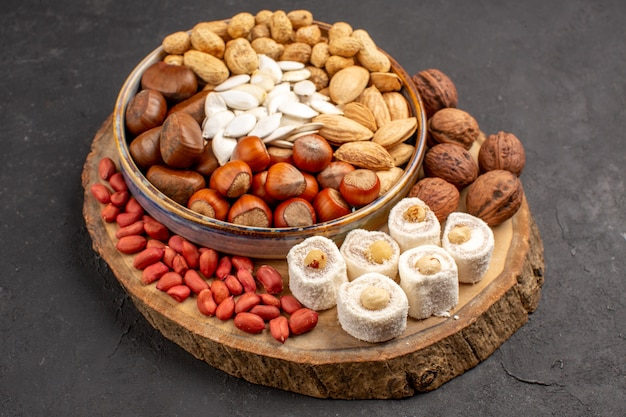 Front view of different nuts with white confitures on dark surface