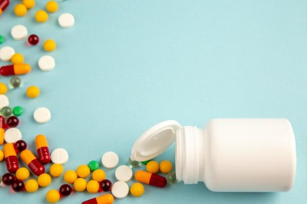 파란색 배경에 플라스틱 플라스크와 전면보기 다른 약 실험실 건강 covid 병원 과학 색상 유행성 약물 바이러스