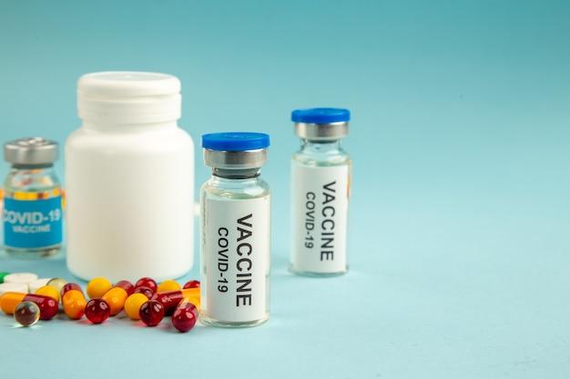 Vista frontale diverse pillole con vaccini su sfondo blu laboratorio salute covid ospedale scienza virus colore farmaco pandemico