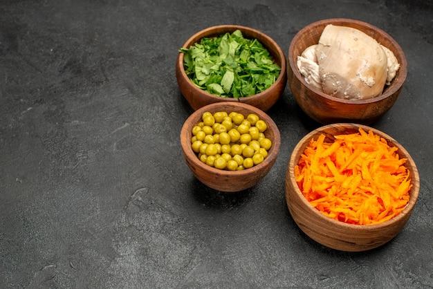 ダークテーブルの健康サラダミールダイエットに鶏肉を添えたさまざまなサラダ材料の正面図