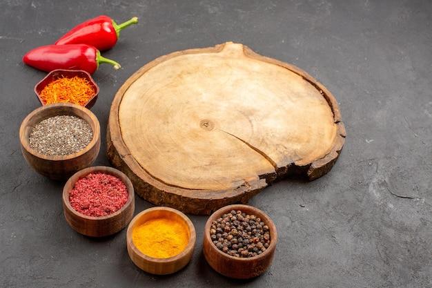 暗い空間の小さな鍋の中のさまざまな調味料の正面図