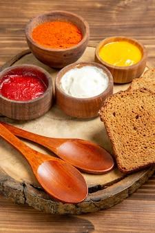 Vista frontale condimenti diversi con pagnotte di pane su spazio marrone