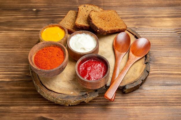 正面図のさまざまな調味料と、茶色の机の上の暗いパンのパン スパイシーな調味料