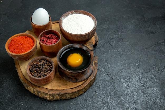 Vista frontale diversi condimenti con farina e uova su uno spazio grigio