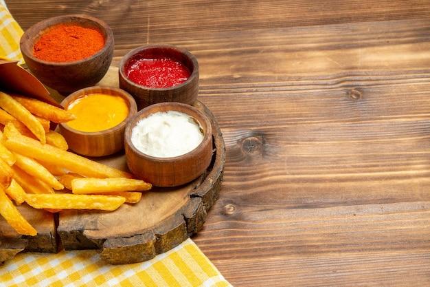 Вид спереди разные приправы с картофелем фри на коричневом деревянном столе, картофельное фаст-фуд
