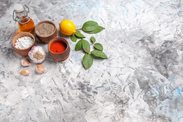 正面図白いテーブルオイルスパイシーフルーツペッパーにレモンとさまざまな調味料