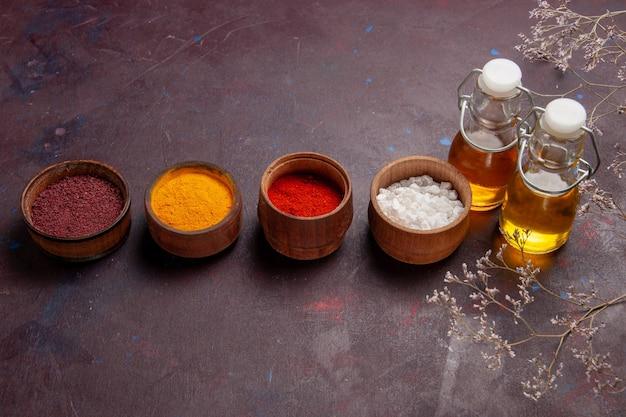 Вид спереди разные приправы с оливковым маслом на темном пространстве