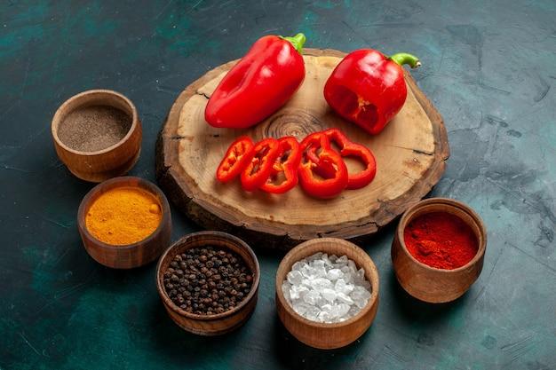 Vista frontale diversi condimenti con peperone rosso su superficie scura