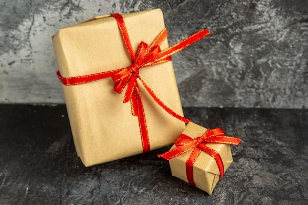Vista frontale regali di diverse dimensioni legati con nastro rosso su sfondo scuro