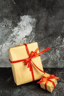 전면 보기 다양한 크기의 선물이 어두운 곳에 빨간 리본으로 묶여 있습니다.