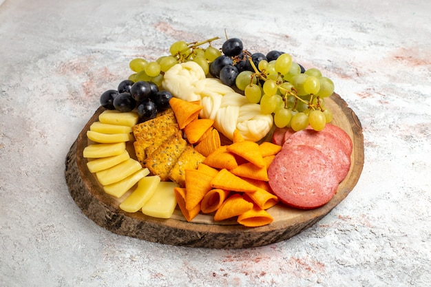 正面図さまざまなスナックcipsソーセージチーズと白いスペースに新鮮なブドウ
