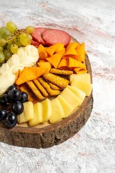 Vista frontale diversi snack cips salsicce formaggio e uva fresca su uno spazio bianco