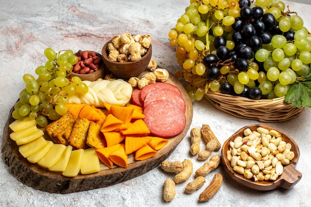 Вид спереди разные закуски свежий виноград сырные чипсы с орехами на белом пространстве