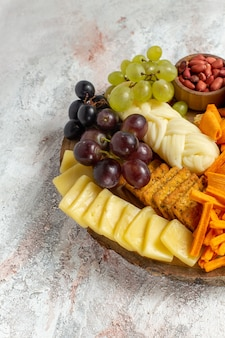 Front view different snacks nuts cips grapes cheese and sausages on a white background nut snack meal food fruit