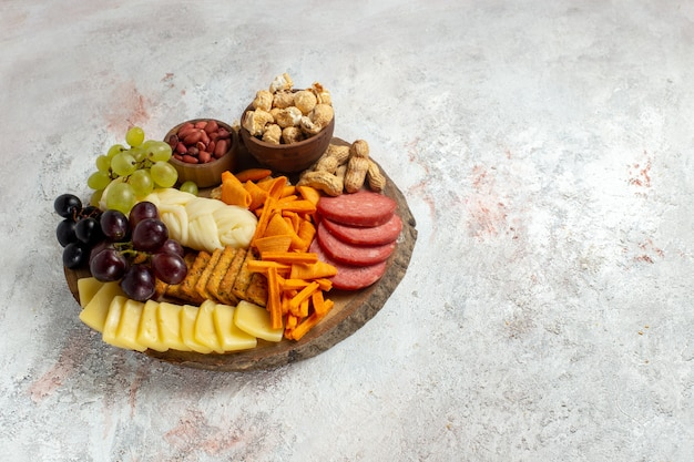 Front view different snacks nuts cips grapes cheese and sausages on white background nut snack meal food fruit