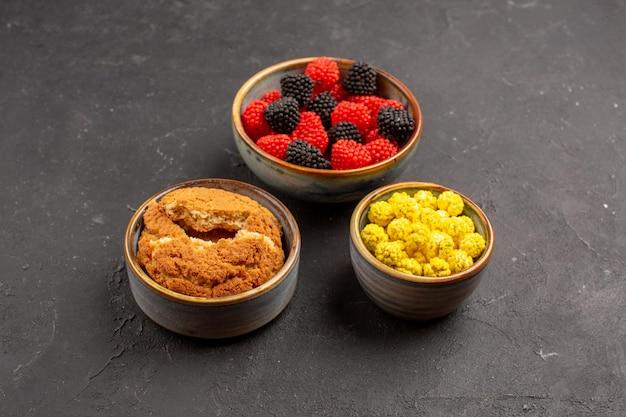 Вид спереди различных сахарных конфитюров внутри маленьких горшочков на темном фоне сахарных конфет вкуснятины цвета ягоды