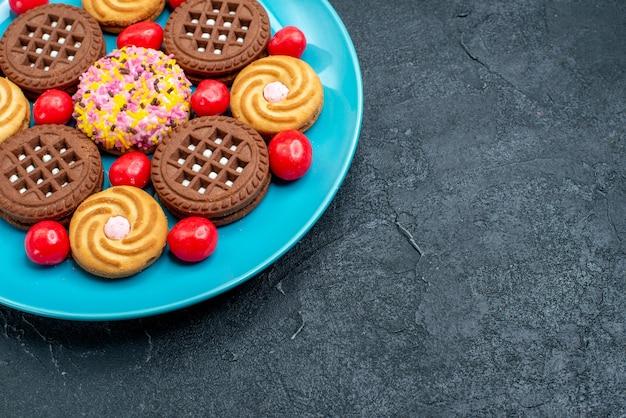 Biscotti di zucchero differenti di vista frontale con le caramelle su un biscotto dolce del biscotto del tè dello zucchero candito di superficie grigia