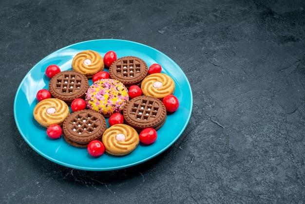 正面図灰色の机の上のキャンディーとさまざまなシュガークッキーキャンディーシュガースウィートティークッキービスケット