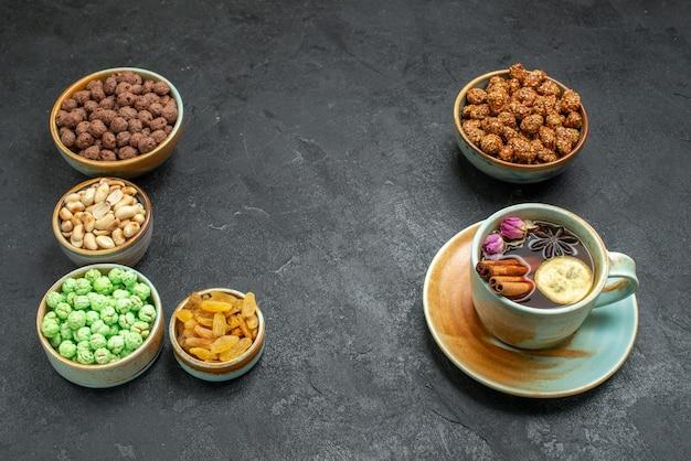 Vista frontale diverse caramelle dolci con noci e tazza di tè su spazio grigio