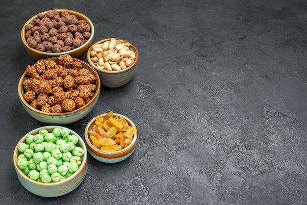 Vista frontale diverse caramelle dolci con noci e uvetta su spazio grigio