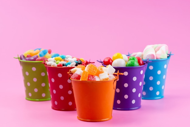 A front view different sweets such as confitures marmalades candies inside baskets on pink, sugar sweet color Free Photo