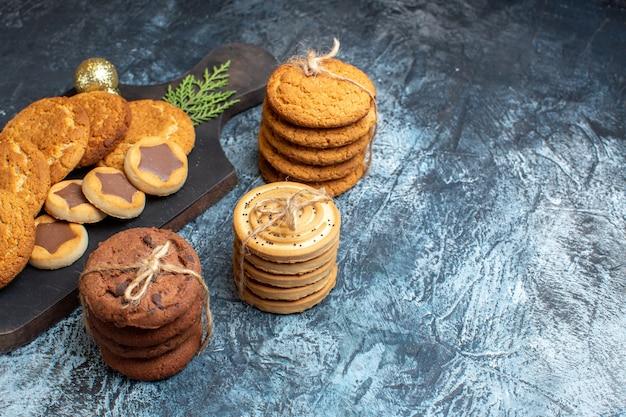Вид спереди разные вкусные печенья на светлой темной поверхности
