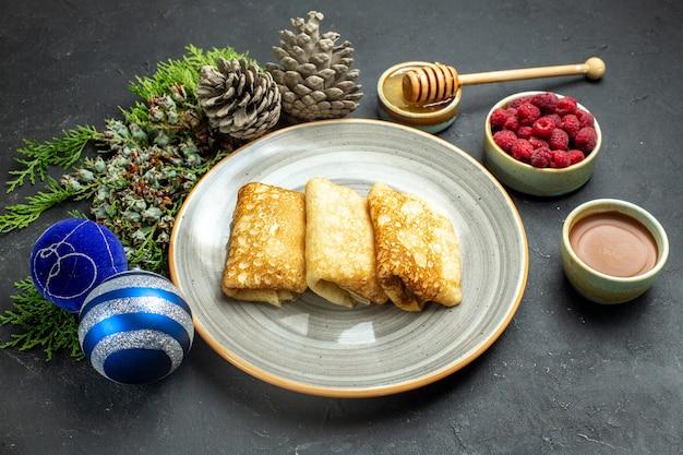 Vista frontale dello sfondo della cena con deliziose frittelle miele e cioccolato lampone e cono di conifere accanto agli accessori del nuovo anno su sfondo nero
