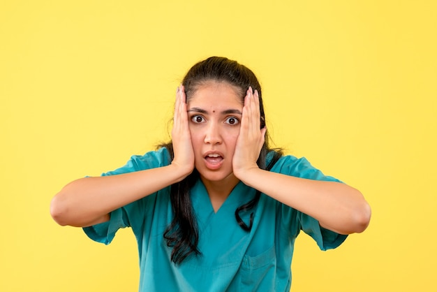 Medico femminile deluso vista frontale in uniforme in piedi su sfondo giallo isolato