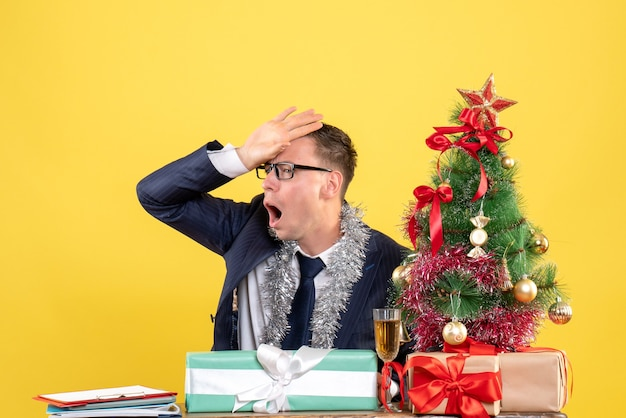 Front view of disappointed man putting hand to his forehead sitting at the table near xmas tree and presents on yellow.