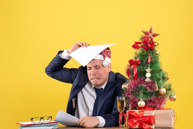 Vista frontale dell'uomo deluso seduto al tavolo vicino all'albero di natale e regali su giallo.