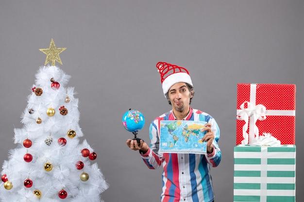 Vista frontale uomo deluso con molla a spirale santa hat holding mappamondo e globo