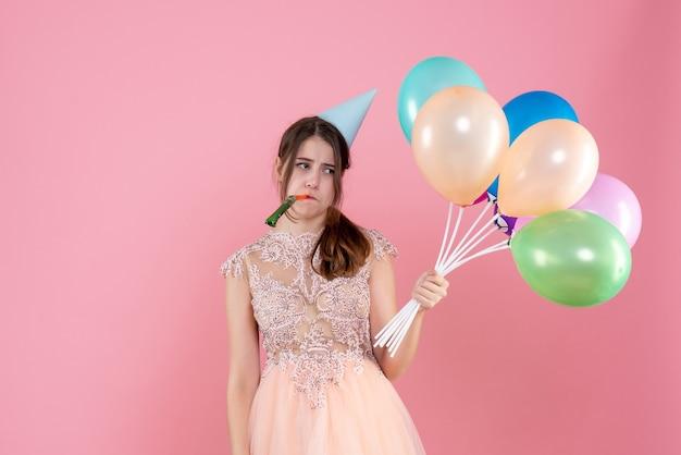 ノイズメーカーを使用して風船を保持しているパーティーキャップを持つ正面図失望したパーティーの女の子