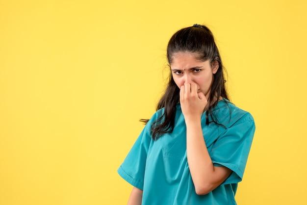 Medico della donna deluso vista frontale in uniforme che sta sul posto giallo della copia del fondo
