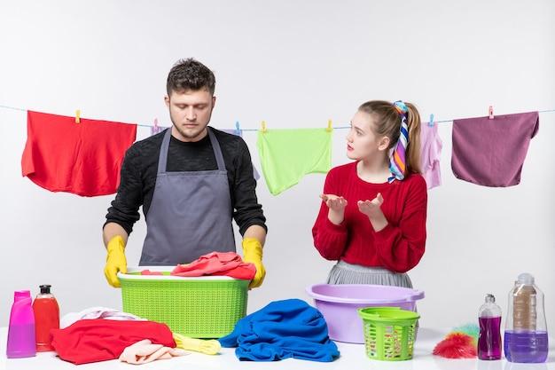 Vista frontale delusa giovane coppia che si parla mentre lava i vestiti sul muro bianco