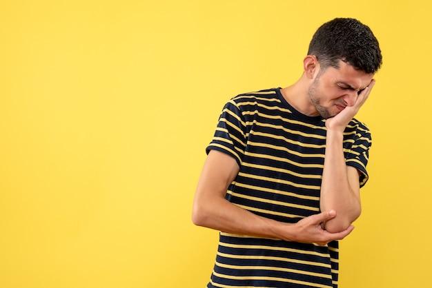 Вид спереди разочарованный молодой мужчина в черно-белой полосатой футболке на желтом изолированном фоне