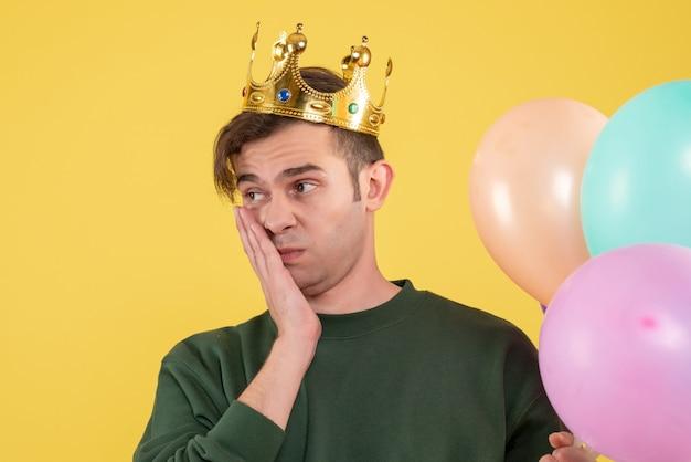 正面図黄色に風船を保持している王冠を持つ失望した若い男