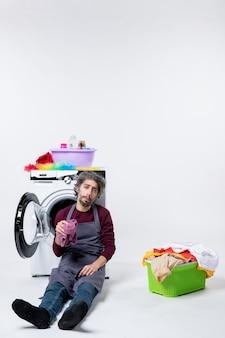 正面図白い背景の上の洗濯かごの近くの洗濯機をリクライニングする意気消沈した家政婦の男