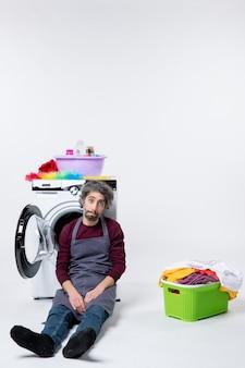 正面図白い背景の上の洗濯かごの近くに座っている意気消沈した家政婦の男