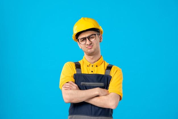 Vista frontale lavoratore maschio scontento in uniforme gialla sull'azzurro
