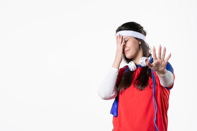 Vista frontale dispiaciuto giovane femmina in abiti sportivi con corde per saltare