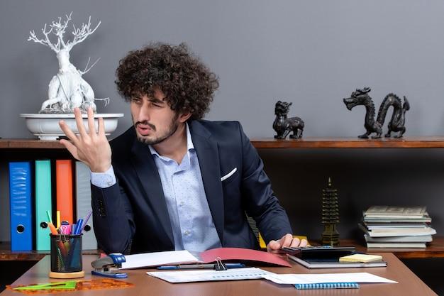 Vista frontale uomo d'affari insoddisfatto seduto alla scrivania in ufficio