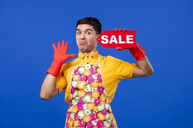 파란색 공간에 판매 기호를 들고 빨간색 배수 장갑을 끼고 불만족스러운 남성 가정부 전면 보기