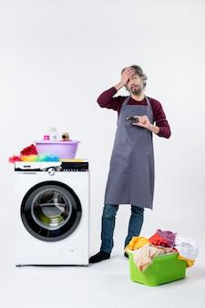 흰색 바탕에 세탁기 근처에 서 있는 카드를 들고 있는 불만족스러운 남자