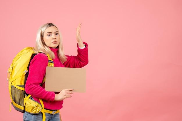 Vista frontale donna insoddisfatta del viaggiatore con lo zaino che tiene cartone