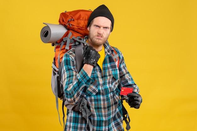 Vista frontale del giovane viaggiatore con zaino e sacco a pelo insoddisfatto con la carta di credito della tenuta del cappello nero