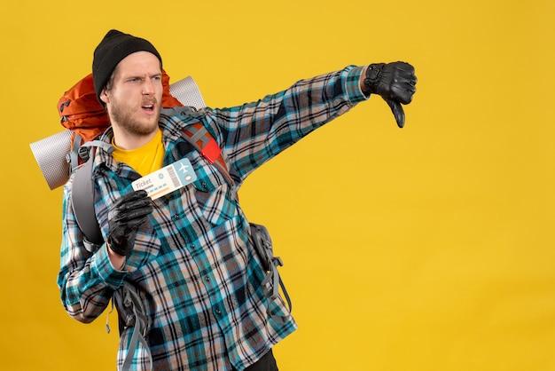 Vista frontale del giovane viaggiatore con zaino e sacco a pelo insoddisfatto con il biglietto aereo della tenuta del cappello nero che dà il pollice verso il basso