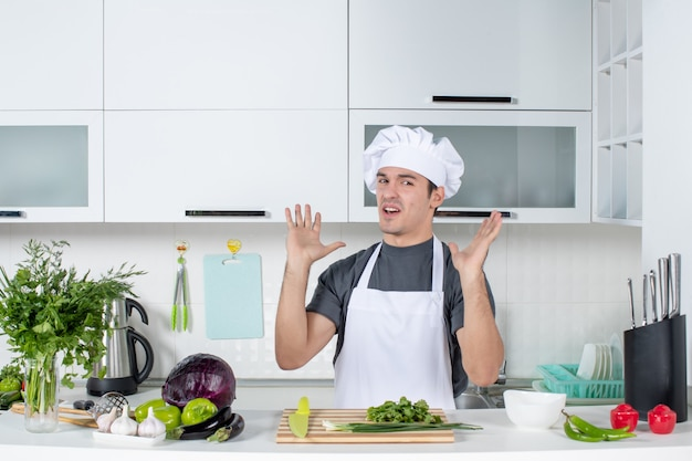 Front view dissatisfied young cook in uniform in kitchen