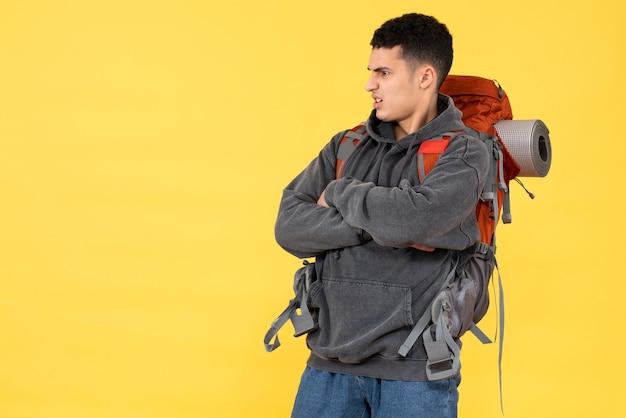 Вид спереди недовольного молодого человека с красным рюкзаком, скрещивающим руки
