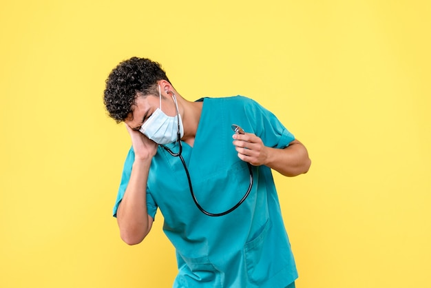 Medico di vista frontale il dottore in maschera ha un mal d'orecchi