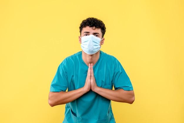 Vista frontale dottore il dottore in maschera prega per la guarigione dei pazienti con coronavirus